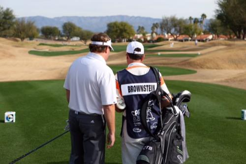 Chad Brownstein-confers with his caddy before he tees off at the Humana Challenge